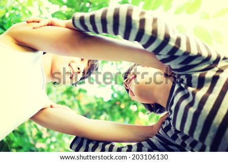 Two kids making a circle of trust and love - stock photo