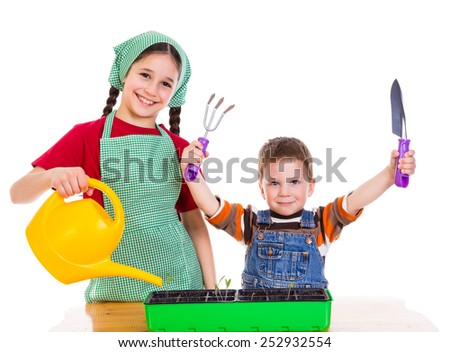 Two kids planting a seedling on the desk, isolated on white - stock photo