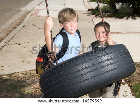 Two kids play on a tire swing after school.