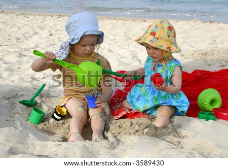 Two kids playing at the beach (one year and three years old)