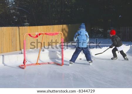 Two kids playing hockey - stock photo
