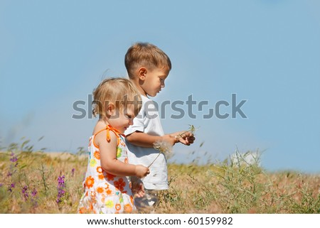 two kids playing in countryside - stock photo