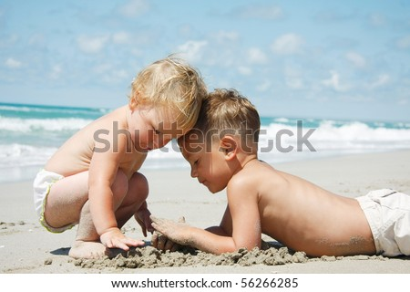 two kids playing in sand on beach