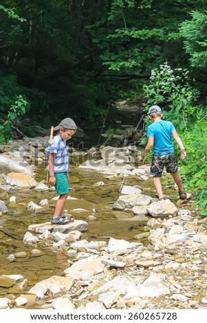 Two kids playing near a mountain stream - stock photo