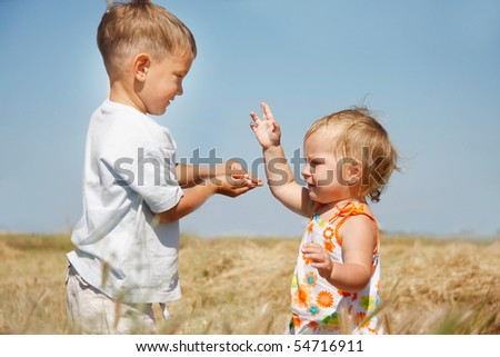 two kids playing on rural background - stock photo