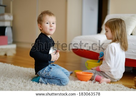 Two kids playing together at home - stock photo