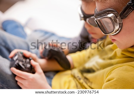 two kids playing wideogames disguised as pilots with real glasses - stock photo
