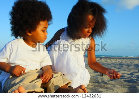 Two kids playing with sand - stock photo