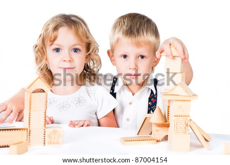 Two kids playing with wooden blocks indoor on white background - stock photo