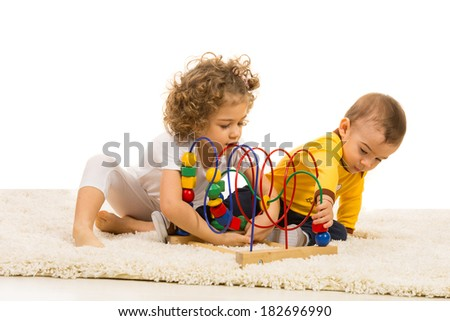 Two kids playing with wooden toy on fur carpet home - stock photo
