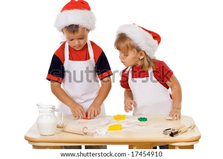 Two kids preparing the christmas cookies - isolated