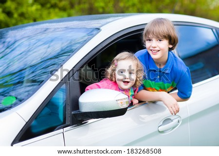 Two kids, school age boy and cute curly toddler girl, enjoy vacation car ride on a summer weekend watching out of window of silver color modern family vehicle after rain with drops on wet front  - stock photo