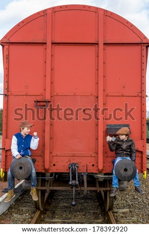 two kids secretly take a ride on the back of a train - stock photo