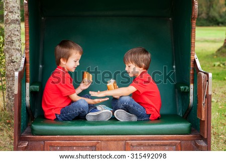 Two kids, sitting in a sheltered bench, playing hand clapping game and eating sandwiches, outdoors in the summer - stock photo