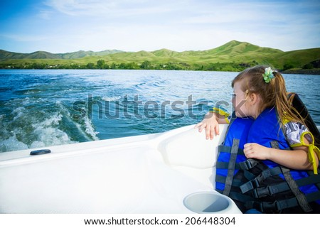 Two kids sitting in the bow of a boat with there life jackets having fun - stock photo
