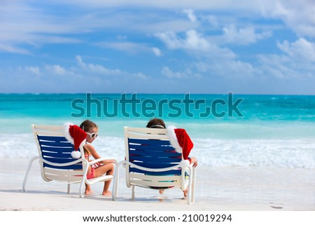 Two kids sitting on chairs with Santa hats at beautiful tropical beach enjoying Christmas vacation - stock photo