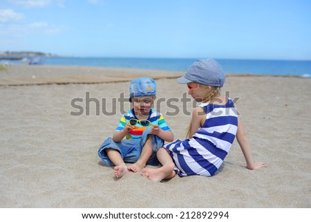 Two kids sitting on the beach - stock photo