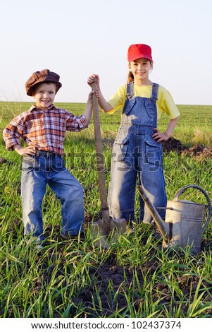 Two kids standing in field with shovel and watering can - stock photo