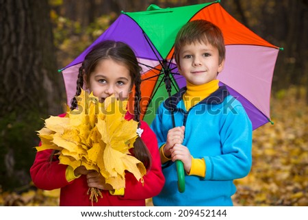 Two kids walking together in autumn park - stock photo