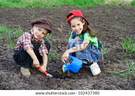 Two kids watering the sprout on field - stock photo