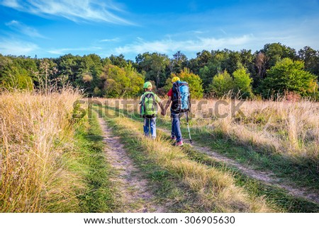 Two kids with backpacks traveling through a meadow - stock photo