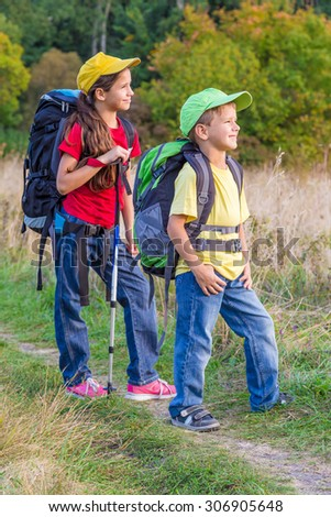 Two kids with backpacks traveling through a meadow