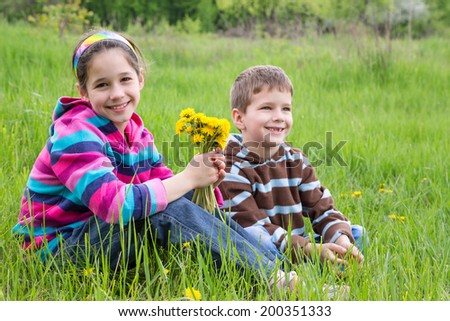 Two kids with bouquet of dandelions sitting on green meadow