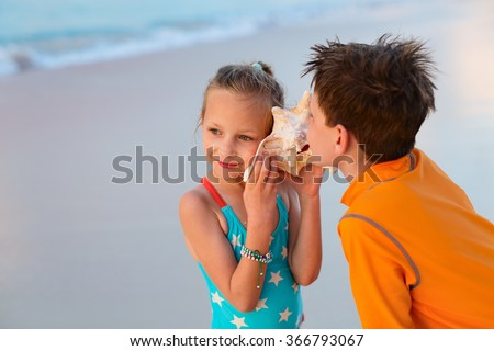 Two kids with giant shell at beach listening to the sea