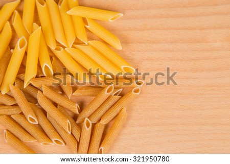 two kinds of pasta on a wooden table - stock photo
