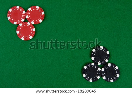 Two kinds of poker chips in two corners of a green poker table. Top view.