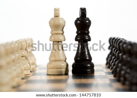 Two kings - black and white chess figures on chess board - stock photo