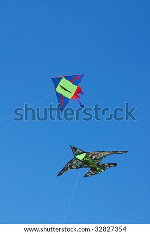 Two kites with a strings flying against a blue sky