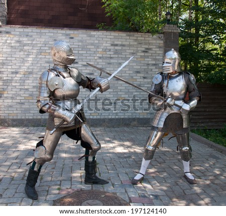 two knights in the ancient metal armor standing near the stone wall - stock photo