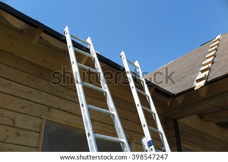 Two ladders at the roof of the wood house under construction against a blue sky