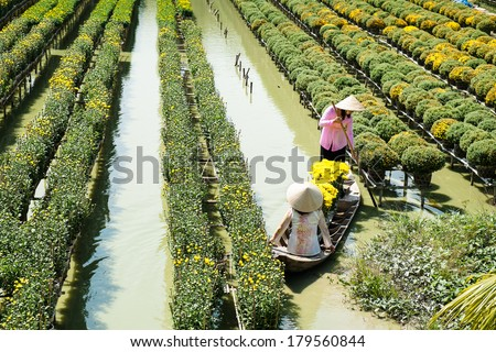 Two ladies are in a boat at the floating flower field in Sa Dec, Dong Thap, Vietnam. Sa Dec is one of the biggest flower stocks in Mekong Delta. - stock photo