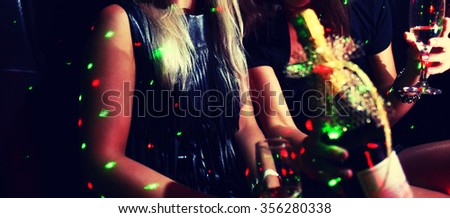 Two ladies drink champagne in night club, toned image. - stock photo