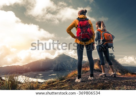 Two ladies hikers standing on top of the mountain and enjoying valley view - stock photo