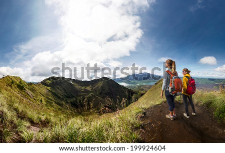Two ladies hikers standing on top of the mountain and enjoying view