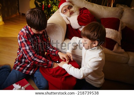 Two lads choosing gifts from red sack with Santa Claus sleeping on sofa near by - stock photo