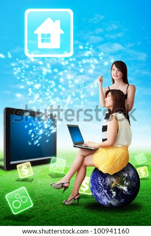 Two lady look at the House icon from tablet computer on grass field : Elements of this image furnished by NASA - stock photo