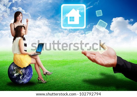 Two lady look at the House icon from the hand : Elements of this image furnished by NASA