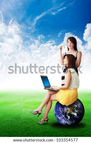 Two lady on grass field and hold notebook computer : Elements of this image furnished by NASA