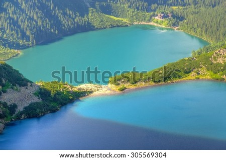 Two lakes in mountains. Two blue mountain lakes surrounded by high summits. Morskie Oko (Eye of the Sea) and Czarny Staw (Black Pond) are the most popular place in High Tatra Mountains, Poland. - stock photo