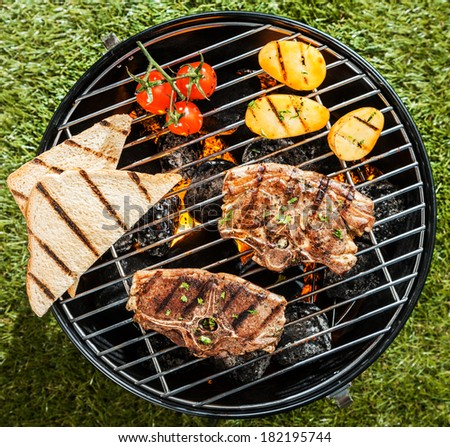Two lamb chops cooking on a BBQ on a portable grill with tomato, potatoes and slices of toast on a sunny summer day outdoors on the grass, overhead view - stock photo