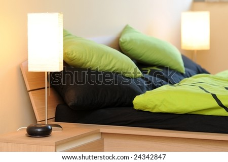 Two lamps in bedroom with green-black beddings