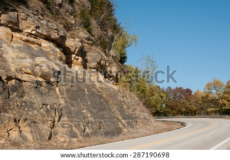 Two-lane country road winding around bluff in bluff lands along Mississippi River in southeast Minnesota  - stock photo
