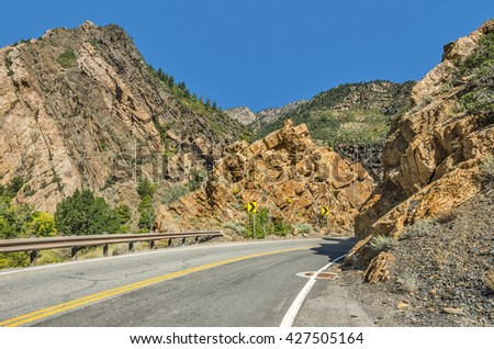 Two-lane winding road through the Wasatch Mountains in Utah with just a hint of fall here and there. - stock photo