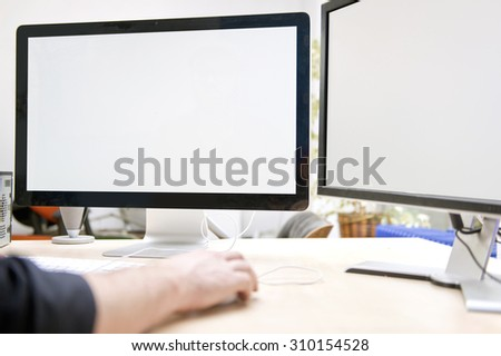 Two large computer screens on a desk, to be used for presentations and mock ups. A computer expert has his hands on the keyboard - stock photo