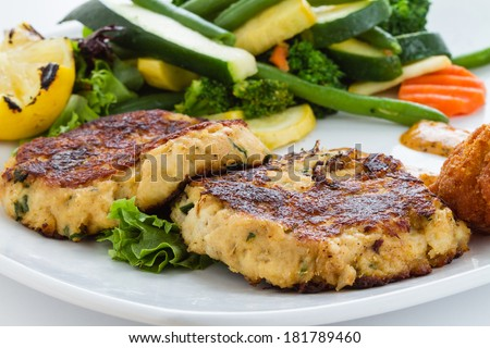 Two large pan fried crab cakes served with fresh vegetables and hush puppies. - stock photo