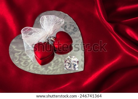 Two large red hearts are tied together with white ribbon and are reflected on heart shaped mirror on red satin draped cloth. The mirror reflects lace and diamond as well. - stock photo
